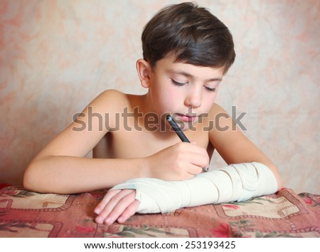 handsome preteen boy with hand in bandage - stock photo