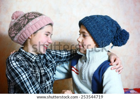 handsome preteen siblings boy and girl in winter knitted hat - stock photo