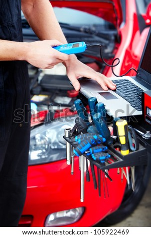 Handsome professional mechanic in auto repair shop. - stock photo