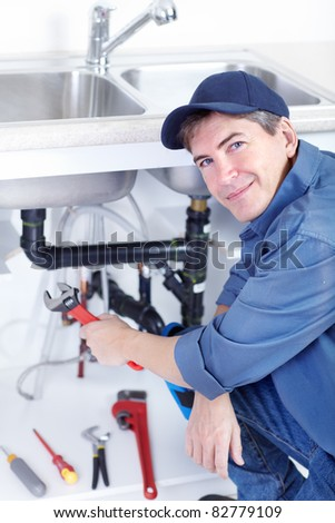 Handsome professional plumber doing sink reparation. Contractor.