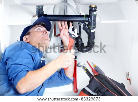 Handsome professional plumber doing sink reparation. Contractor. - stock photo