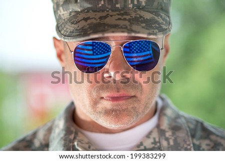 Handsome proud american man soldier in trendy sunglasses outdoors - stock photo