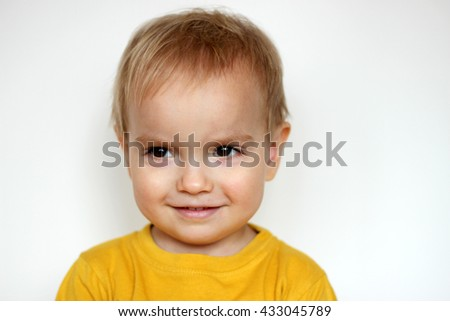 Handsome rapturous small toddler boy in yellow T-shirt smiling sincerely and shied over white background, face emotions concept, indoor close-up - stock photo