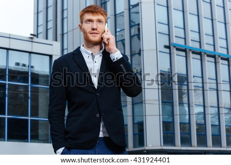 Handsome redhead businessman talking on the phone outdoors with glass bulding on background
