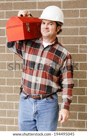 Handsome repairman carries his tool box on his shoulder.   - stock photo