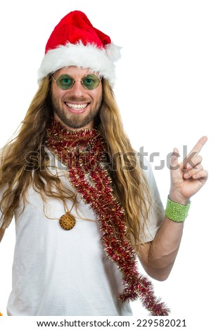 Handsome retro hippie in Santa hat pointing at copy-space. Isolated on white. - stock photo