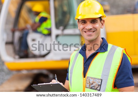 handsome road construction supervisor with clipboard - stock photo