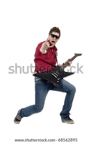 Handsome rock star playing the guitar gesturing rock sign, isolated