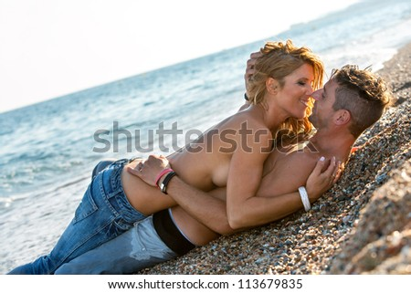 Handsome romantic couple embracing on pebble beach. - stock photo