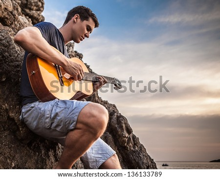 Handsome romantic guitarist play music siting on beach rock. - stock photo