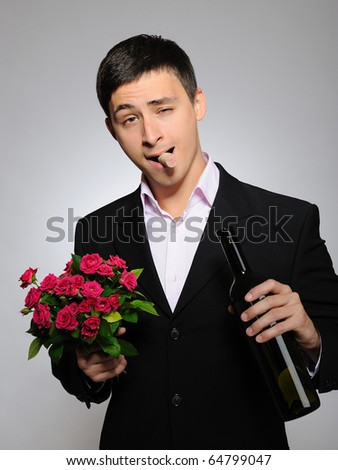 Handsome romantic young man holding rose flower and vine bottle  prepared for a date. gray background - stock photo