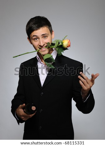 Handsome romantic young man holding rose flower and vine bottle  prepared for a valentines day. gray background - stock photo