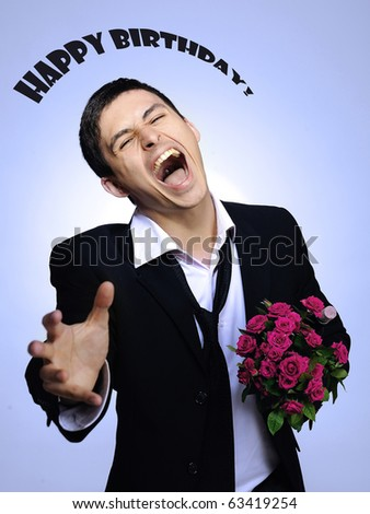 Handsome romantic young man holding rose flower. gray background. happy birthsday sighn - stock photo