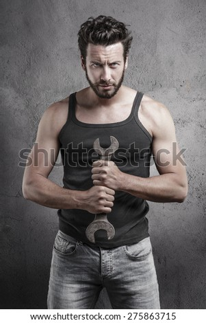 Handsome rough casual man standing holding a wrench over a textured grey background - stock photo