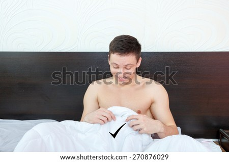 Handsome satisfied man sure in himself showing under cover in bedroom strong penis erection in the morning . Photo of healthy male potency
