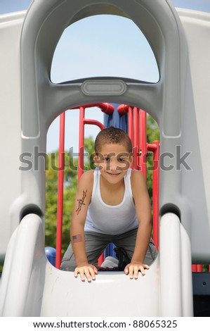Handsome School Age Boy Mohawk Hairstyle Smiling Looking at Camera on Playground Slide