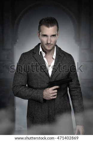 Handsome secret agent holding a gun