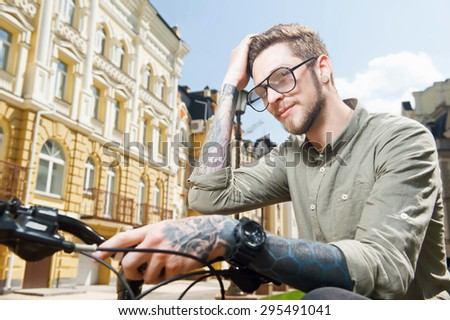 Handsome self-confident hipster guy is touching his hair flirtingly. He is sitting on bicycle. He has tattoo and glasses - stock photo