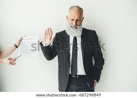 handsome senior businessman refusing to sign contract on white background