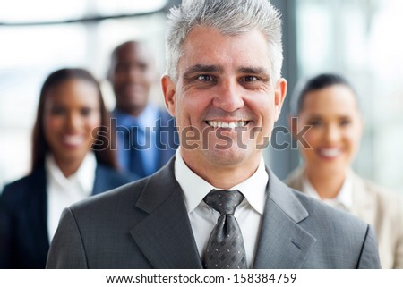 handsome senior businessman standing with co-workers on background - stock photo