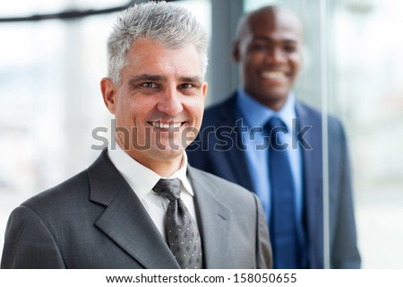 handsome senior businessman with colleague on background - stock photo