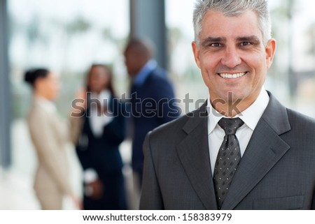 handsome senior businessman with colleagues on background - stock photo
