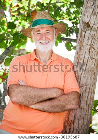 Handsome senior man wearing a panama hat and standing in the shade. - stock photo