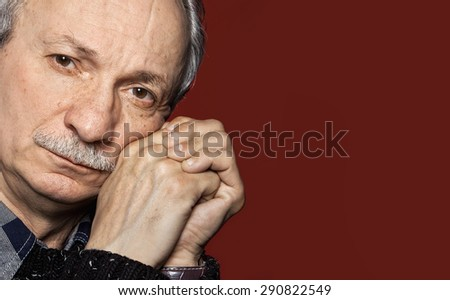Handsome senior man with a skeptical expression on dark red background with copy-space