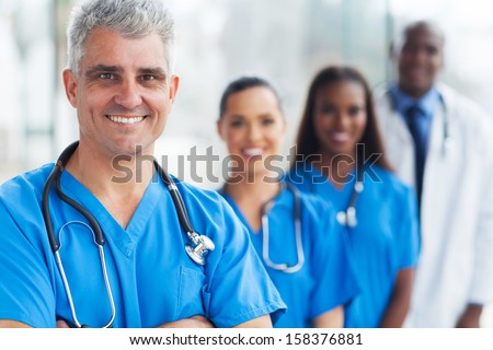 handsome senior medical doctor and team at hospital - stock photo