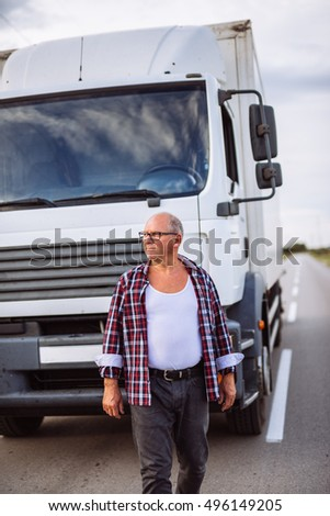 Handsome senior truck driver standing in front of his truck.