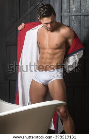 Handsome sensual sexy young man in white panties and terry bathrobe with bare muscular torso and beautiful body indoor near bathtub in bath room, vertical picture - stock photo