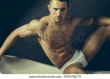 Handsome sensual sexy young stylish man in white panties bare muscular torso and beautiful body indoor sitting on bathtub in bath room on studio background, horizontal picture