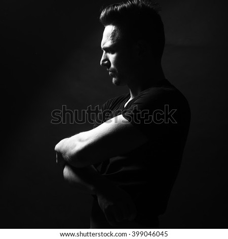 Handsome sensual sexy young stylish thoughtful man in black shirt with fashionable hairdo undressing with bare muscular torso and beautiful body indoor on studio background, sauqre picture