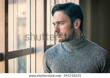 Handsome serious man standing inside modern building next to big window, wearing wool sweater,  looking out - stock photo