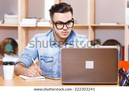 Handsome serious man, wearing in casual blue shirt and glasses, looking at laptop screen and writing something in his notebook, on the bookshelves background, waist up - stock photo