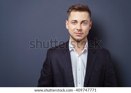 Handsome serious young man standing against a dark background with copy space looking at the camera with a quiet smile - stock photo