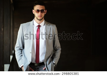 Handsome sexual serious unshaven businessman in grey jacket white shirt red tie and sun glasses standing outdoor with hands in pockets on black background copyspace, horizontal picture - stock photo