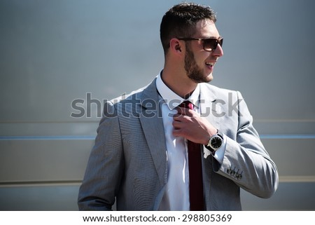 Handsome sexual smiling unshaven businessman in grey jacket white shirt sun glasses standing outdoor holding hand near red tie on gray background copyspace, horizontal picture - stock photo
