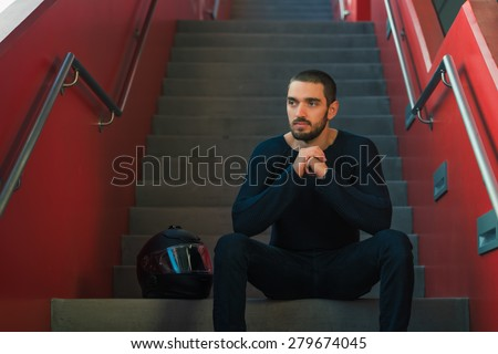 Handsome sexy and casual young man with helmet sitting on stairs. High resolution photo. - stock photo