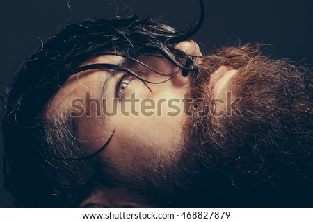 handsome sexy bearded young man hipster with long beard and mustache has wet hair on serious hairy face, closeup