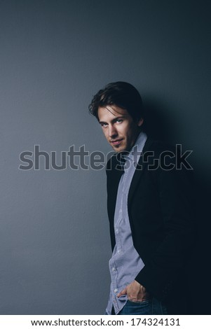 Handsome sexy businessman standing nonchalantly with his hand in his pocket and his suit jacket undone on a grey background with copyspace