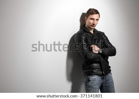 handsome sexy man in a leather jacket near white wall - stock photo