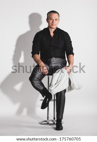 Handsome sexy man in black shirt sitting on bar chair - stock photo