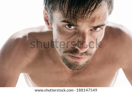 Handsome sexy naked young man with a goatee beard and an intense expression leaning forwards towards the camera with a glowering gaze - stock photo
