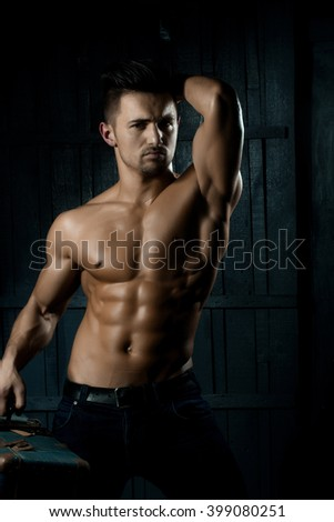 Handsome sexy sensual muscular stylish young man topless with bare torso and beautiful body standing near stairs with hard big retro suit case indoor on wooden background, vertical picture - stock photo