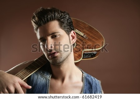 Handsome sexy young man musician guitar player portrait on brown