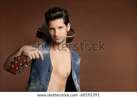 Handsome sexy young man musician guitar player portrait on brown - stock photo