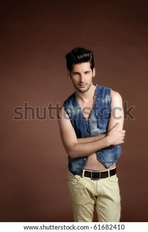 Handsome sexy young man portrait denim jacket brown background - stock photo