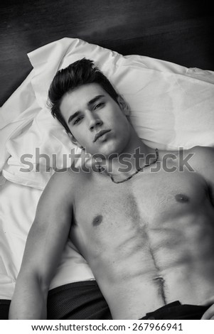 Handsome shirtless athletic young man laying in bed at night looking at camera, seen from above