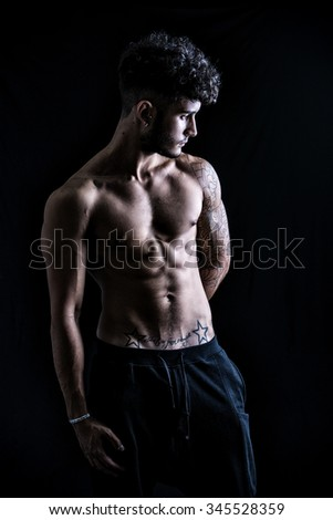 Handsome shirtless athletic young man, looking to a side in studio shot, isolated on black background, dramatic lighting - stock photo